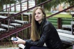Mirada hermosa joven de la muchacha y música que escucha en su teléfono móvil que los estadios viejos bench Imagenes de archivo