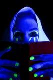 Mirada ligera negra de los ojos del libro de la mujer encima Foto de archivo libre de regalías