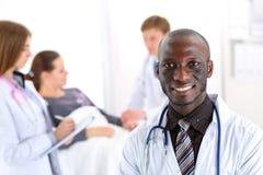 Mirada masculina sonriente negra del doctor in camera foto de archivo libre de regalías