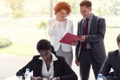 Mirada masculina y femenina de los empleados en el informe de negocios fotografía de archivo