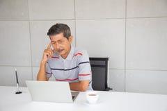 Mirada mayor del hombre de negocios de Asia en el ordenador port?til y el pensamiento foto de archivo libre de regalías