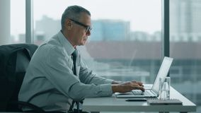 Mirada mayor del hombre de negocios en el teléfono y trabajo con el ordenador en oficina moderna almacen de metraje de vídeo