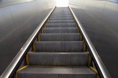 Mirada para arriba de una escalera móvil a la luz blanca imagen de archivo