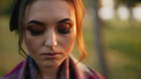 Mirada pensativa a un lado, abajo y en de la cámara de la muchacha seria en parque del otoño metrajes