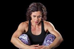 Mirada que se sienta de la mujer muscular abajo de contemplativo Imagen de archivo libre de regalías