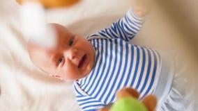 Mirada recién nacida del bebé en la vuelta del juguete del carrusel sobre cama almacen de metraje de vídeo