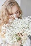 Mirada romántica rubia rizada, ojos hermosos Wildflowers blancos en manos Vestido y pelo rizado, retrato de la luz blanca de la m fotografía de archivo libre de regalías