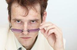 Mirada severa del hombre joven sobre gafas Imagen de archivo libre de regalías