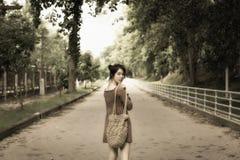 mirada soñadora del soporte hermoso asiático de la señora en el centro del camino y Imagen de archivo