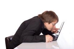 Mirada soñolienta del hombre de negocios de cerca su ordenador portátil Foto de archivo