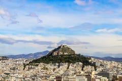 Mirada sobre los tejados a la colina de Lycabettus - el punto más alto de Atenas Grecia con la iglesia de San Jorge y un resturan foto de archivo libre de regalías