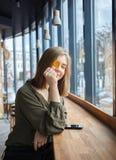 Mirada sonriente de la muchacha adolescente hermosa del estudiante en cámara en el café de la calle que se sienta cerca de la ven Imagen de archivo