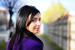 Mirada sonriente de la muchacha detrás Fotografía de archivo libre de regalías