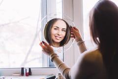 mirada sonriente de la muchacha en el espejo imagen de archivo