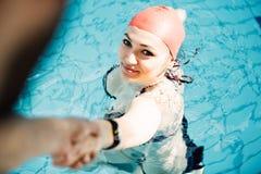 Mirada sonriente del casquillo hermoso de la mujer a la cámara en la frontera de la piscina Imágenes de archivo libres de regalías