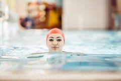 Mirada sonriente del casquillo hermoso de la mujer a la cámara en la frontera de la piscina Foto de archivo libre de regalías
