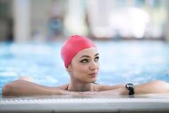 Mirada sonriente del casquillo hermoso de la mujer a la cámara en la frontera de la piscina Imagenes de archivo