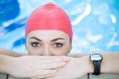 Mirada sonriente del casquillo hermoso de la mujer a la cámara en la frontera de la piscina Imagen de archivo