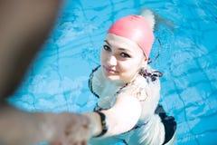 Mirada sonriente del casquillo hermoso de la mujer a la cámara en la frontera de la piscina Imagen de archivo libre de regalías