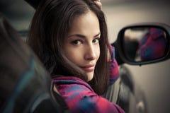 Mirada sonriente joven de la mujer hacia fuera de la ventanilla del coche Imagenes de archivo