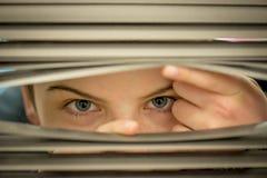 Mirada a través de las persianas imagen de archivo libre de regalías