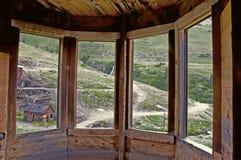 Mirada a través de una ventana de bahía en un pueblo fantasma viejo. Foto de archivo libre de regalías