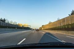 Mirada a través del frente arrojado de un coche a la carretera Imagen de archivo libre de regalías