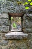 Mirada a través de la ventana de la casa de piedra Fotografía de archivo libre de regalías