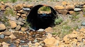 Mirada a través del tubo acanalado aherrumbrado del metal en tierra rocosa Imagen de archivo