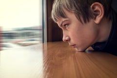 Mirada triste del adolescente en la ventana Foto de archivo