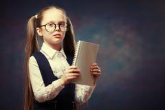 Mirada uniforme de los vidrios del desgaste de la colegiala en el cuaderno Tono del color foto de archivo