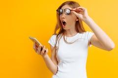 Miradas sorprendidas de la muchacha chocadas en el teléfono en un fondo amarillo imagen de archivo