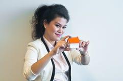 Miradas y controles de la mujer que una casa modela en el fondo blanco Fotografía de archivo