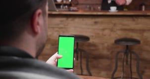 Miradas y golpes fuertes del hombre en un teléfono con la pantalla de visualización verde almacen de video