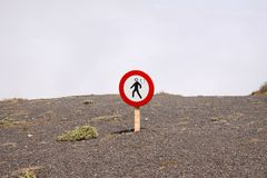 Mirador del Rio - Lanzarote: Isolated round sign do not walk here above clouds on dry stony ground at steep mountain side royalty free stock photos