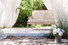 Miradouro moderno luxuoso com mobília e as cortinas macias dentro do jardim Pavilhão da cerimônia de casamento do verão Imagem de Stock