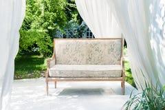 Miradouro moderno luxuoso com mobília e as cortinas macias dentro do jardim Pavilhão da cerimônia de casamento do verão Foto de Stock Royalty Free