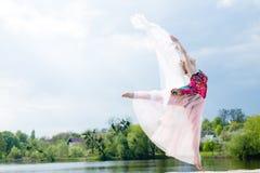 Mirakeldanser: beeld van wonderfully dansend blond meisje in lichte kleding bij watermeer op de zonneschijn blauwe hemel van verl Stock Foto