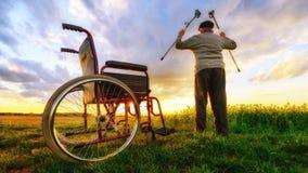 Mirakelterugwinning: De oude mens staat van rolstoel op en heft omhoog handen op Royalty-vrije Stock Afbeelding