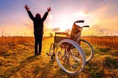 Mirakelterugwinning: het jonge meisje staat van rolstoel op en heft op Stock Fotografie