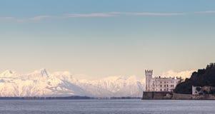 Miramar Kasteel met Italiaanse Alpen op achtergrond Triëst Italië royalty-vrije stock afbeeldingen
