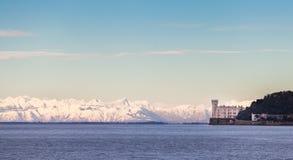 Miramar slott med italienska fjällängar i bakgrund italy trieste Arkivfoto