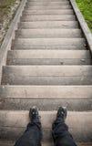 Mirando abajo en las piernas y la escalera masculinas Foto de archivo