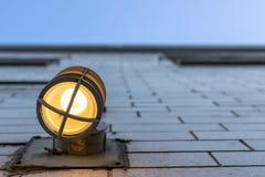 Mirando para arriba una pared exterior alta, con hacia fuera borrosa una lámpara en el primero plano imagen de archivo