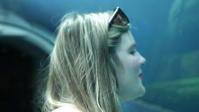 Mirando sorprende a una mujer nadada de los animales cerca en objeto expuesto subacuático del acuario de la bóveda almacen de video