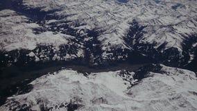 Mirando a través de los aviones de la ventana durante vuelo un italiano nevado y las montañas de Osterreich con el cielo azul fue metrajes