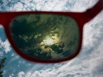 Mire en el sol a través de las gafas de sol protegidas ULTRAVIOLETA fotos de archivo libres de regalías