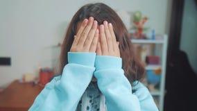 Mire a escondidas un abucheo la niña cubrió sus ojos para hacer frente con su forma de vida que esperaba del escondite de las man almacen de metraje de vídeo