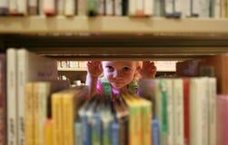 Mire a escondidas un libro Fotos de archivo libres de regalías