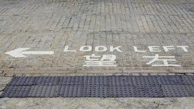 Mire a la izquierda, advertencia del camino del peligro en el camino Placa de calle de la dirección Fotografía de archivo libre de regalías